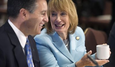 Nevada Gov. Brian Sandoval, chairman of the Education and Workforce Committee, left, speaks with New Hampshire Gov. Maggie Hassan, vice chair, at the committee's morning session at the National Governors Association Winter Meeting in Washington, Sunday, Feb. 22, 2015. (AP Photo/Cliff Owen)