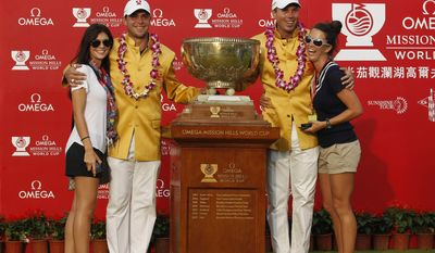 Gary Woodland, second left, of the U.S. poses with his girlfriend Gabby Granado, left, as teammate Matt Kuchar hugs his wife Sybi after the American pair won the World Cup golf tournament at the Mission Hills Blackwater course in Haikou, Hainan province, Southern China, Sunday, Nov. 27, 2011. (AP Photo/Kin Cheung)']