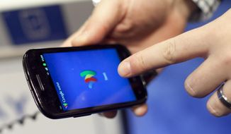 In this Jan. 17, 2012 photo, a person tries a smartphone loaded with Google Wallet at the National Retail Federation in New York. Google is teaming up with three major U.S. wireless carriers in an effort to prod more people into using its mobile wallet and undercut the rapid success of Apple's rival payment service. (AP Photo/Mark Lennihan, File)