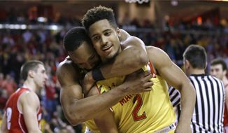 Maryland's Dez Wells hugs guard Melo Trimble (2) in the second half of an NCAA college basketball game against Wisconsin, Tuesday, Feb. 24, 2015, in College Park, Md. Trimble and Wells contributed a combined 42 points to Maryland's 59-53 upset win. (AP Photo/Patrick Semansky)