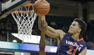 Virginia's Isaiah Wilkins, right, blocks a shot by Wake Forest's Madison Jones, left, during the first half of an NCAA college basketball game in Winston-Salem, N.C., Wednesday, Feb. 25, 2015. (AP Photo/Chuck Burton)
