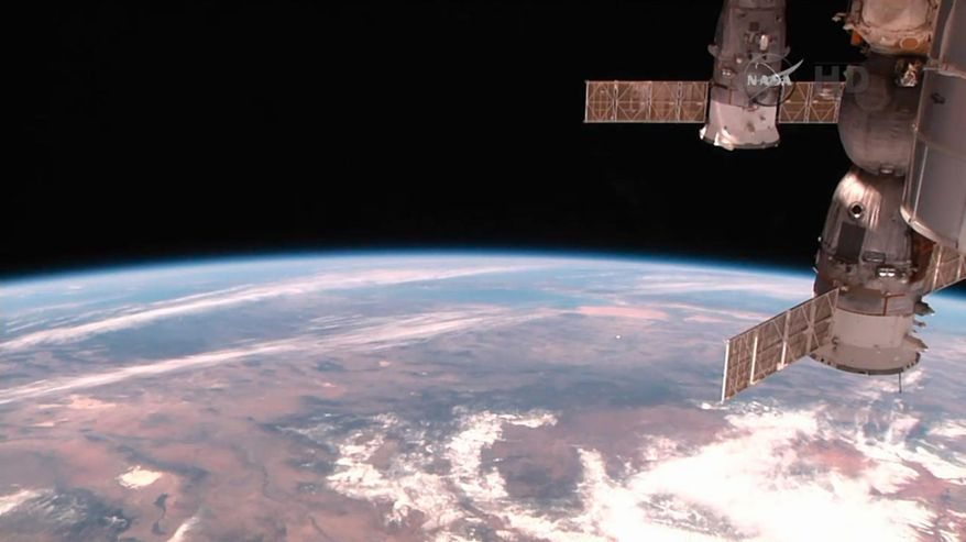 This image made from video provided by NASA shows part of the International Space Station with the Earth in the background on Wednesday, Feb. 25, 2015. (AP Photo/NASA)
