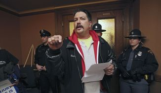 Randy Bryce, of Caledonia, with Iron Workers Local 8, reads his testimony outside a hearing room that is barricaded by police, after he was not able to speak during a meeting for a right-to-work bill at the Wisconsin State Capitol in Madison, Wis., Tuesday, Feb. 24, 2015. (AP Photo/Wisconsin State Journal, Amber Arnold)