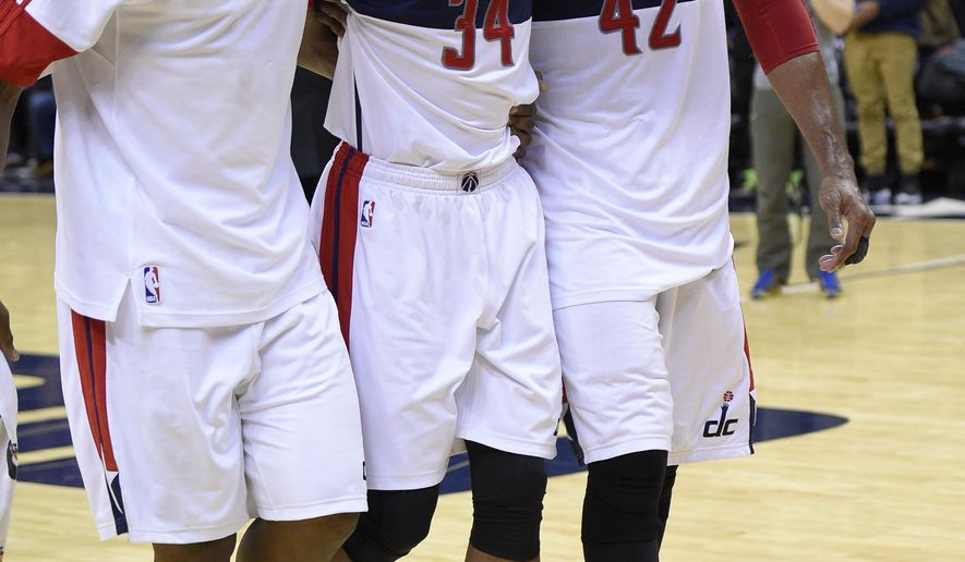Washington Wizards forward Paul Pierce (34) is helped off the court by Kevin Seraphin, left, and Nene (42), of Brazil, after an NBA basketball game against the Golden State Warriors, Tuesday, Feb. 24, 2015, in Washington. The Warriors won 114-107. (AP Photo/Nick Wass)