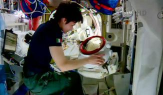 In this image made from video provided by NASA, Italian astronaut Samantha Cristoforetti checks the helmet of astronaut Terry Virts inside the International Space Station on Wednesday, Feb. 25, 2015. Virts reported the water while he waited in the air lock for Wednesday's spacewalk to formally conclude. (AP Photo/NASA) ** FILE **