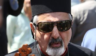 Ignatius Joseph III Younan, Patriarch of Antioch of the Syriac Catholics, leaves a church where displaced Iraqi Christian families, who fled the village of Hamdaniya near Mosul, had taken refuge, in Irbil, Iraq, Sunday, June 29, 2014. Thousands of Iraqi Christians flocked back home Wednesday, days after they fled their villages that came under attack by Sunni insurgents led by the al-Qaida inspired Islamic Sate in Iraq and the Levant, after ruling Kurdish forces told them it was safe to return. (AP Photo/Hussein Malla)