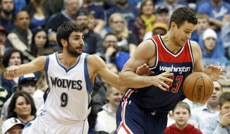 Minnesota Timberwolves' Ricky Rubio, left,  of Spain, knocks the ball away from Washington Wizards' Kris Humphries in the first quarter of an NBA basketball game, Wednesday, Feb. 25, 2015, in Minneapolis. (AP Photo/Jim Mone)
