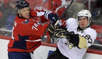 Washington Capitals defenseman John Carlson (74) pushes Pittsburgh Penguins center Sidney Crosby (87) against the boards during the third period of an NHL hockey game, Wednesday, Feb. 25, 2015, in Washington. The Penguins won 4-3. (AP Photo/Nick Wass)