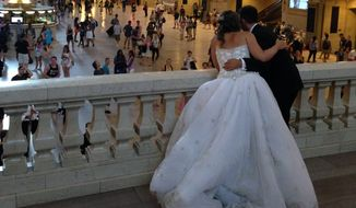 A bride and groom lean over the east balcony as they pose for a photograph in Grand Central Terminal in New York. Grand Central Station. (AP Photo/Donald King)