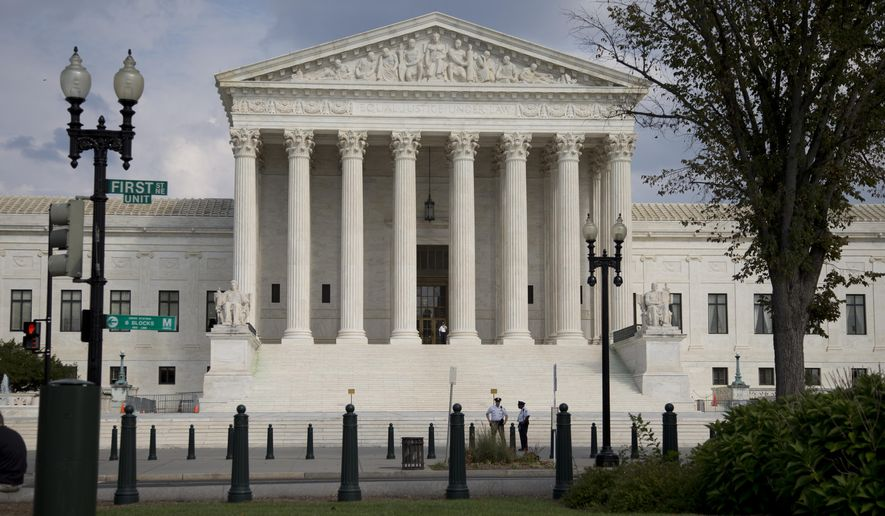 FILE - The Supreme Court Building is shown in this, Thursday, Sept. 18, 2014 file photo in Washington. Prosecutors are taking a hard line with demonstrators who participated in a rare disruption inside the U.S. Supreme Court, adding additional charges against them and saying disrupting the high court is different from other protests in the nation's capital.  (AP Photo/Carolyn Kaster, File)