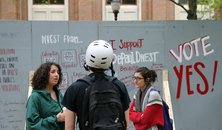 "In this Tuesday, May 13, 2014, file photo, Dina Abdalla, left, and Leila Abdul Razzaq, of Students for Justice in Palestine, talk to a fellow student in front of an ""apartheid wall"" their group created to promote voting for divestment at DePaul University in Chicago. (AP Photo/Chicago Tribune, Brian Cassella) ** FILE **"
