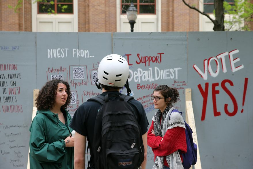 """In this Tuesday, May 13, 2014, file photo, activists with Students for Justice in Palestine talk to a fellow student in front of an """"apartheid wall"""" their group created to promote voting for divestment at DePaul University in Chicago. Students for Justice in Palestine is central to a Department of Education investigation launched in January 2020 into possible anti-Semitism at UCLA (AP Photo/Chicago Tribune, Brian Cassella) ** FILE **"""