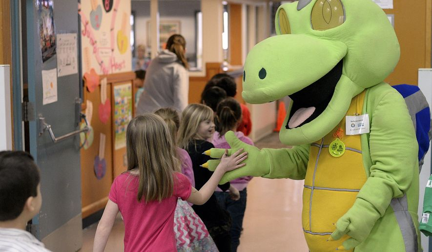 ADVANCE FOR RELEASE SUNDAY, MARCH 1, 2015, AT 1:22 A.M. AKST. AND THEREAFTER - In this Feb. 20, 2015 photo Houghtaling Elementary School students greet Reflectorsaurus in Ketchikan, Alaska. The Alaska Department of Transportation's dinosaur visited the school to help teach kids about wearing reflective clothes at night and to be careful when crossing the street. (AP Photo/Ketchikan Daily News, Taylor Balkom) ADVANCE FOR RELEASE SUNDAY AND THEREAFTER