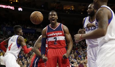 Washington Wizards' John Wall (2) reacts after a basket between, from left to right, Philadelphia 76ers' Nerlens Noel, Luc Mbah a Moute, of Cameroon, and Isaiah Canaan during the first half of an NBA basketball game, Friday, Feb. 27, 2015, in Philadelphia. (AP Photo/Matt Slocum)