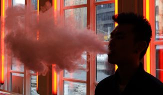 A patron exhales vapor from an e-cigarette at the Henley Vaporium in New York. (Associated Press) **FILE**