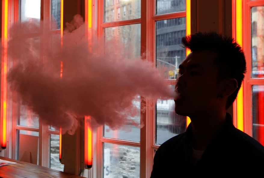 A patron exhales vapor from an e-cigarette at the Henley Vaporium in New York. (Associated Press) **FILE**