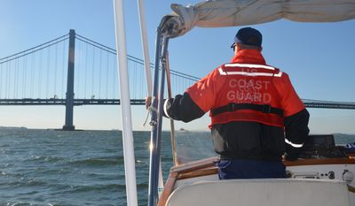 A member of the US Coast Guard looks at the Verrazano-Narrows Bridge from his boat in New York City, USA, 06 October 2014. Photo by: Chris Melzer/picture-alliance/dpa/AP Images