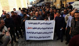 Iraqis hold a protest a day after Islamic State militants posted an online video showing them smashing rare ancient artifacts in a museum, in Baghdad, Iraq, Friday, Feb. 27, 2015. The protesters held a banner denouncing the destruction of the artifacts and call upon the Iraqi government to protect archeological sites in the country. (AP Photo/Karim Kadim)