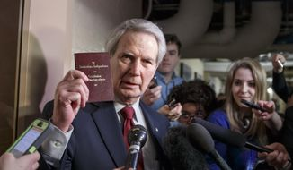 Rep. Walter B. Jones, R-N.C., holds up a copy of the Constitution while talking to reporters as House Republicans emerge from a closed-door meeting on how to deal with the impasse over the Homeland Security budget, at the Capitol in Washington, Thursday, Feb. 26, 2015. (AP Photo/J. Scott Applewhite)