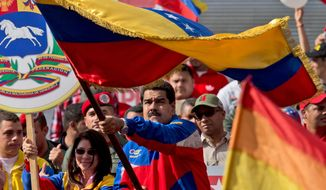 Venezuela's President Nicolas Maduro, center, waves a national flag during a rally in Caracas, Venezuela, Saturday, Feb. 28, 2015. Venezuelans took to the streets of Caracas in dueling demonstrations on Saturday, with one group calling attention to a crackdown on opponents of the government and another showing support for the embattled socialist administration. At left is Venezuela's first lady Cilia Flores. (AP Photo/Fernando Llano)