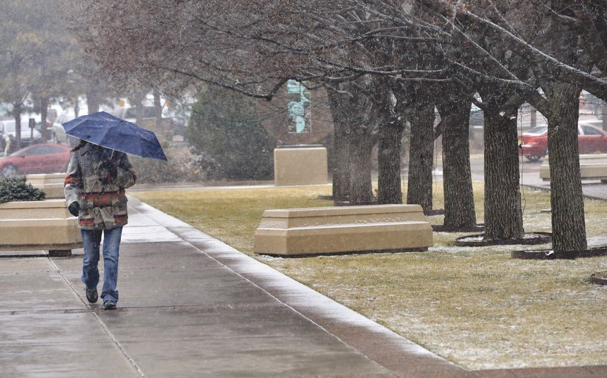 A woman walks up the sidewalk to the New Mexico State Capitol as  snow began to fall Friday, Feb. 27, 2015. (AP Photo/The Santa Fe New Mexican, Clyde Mueller)