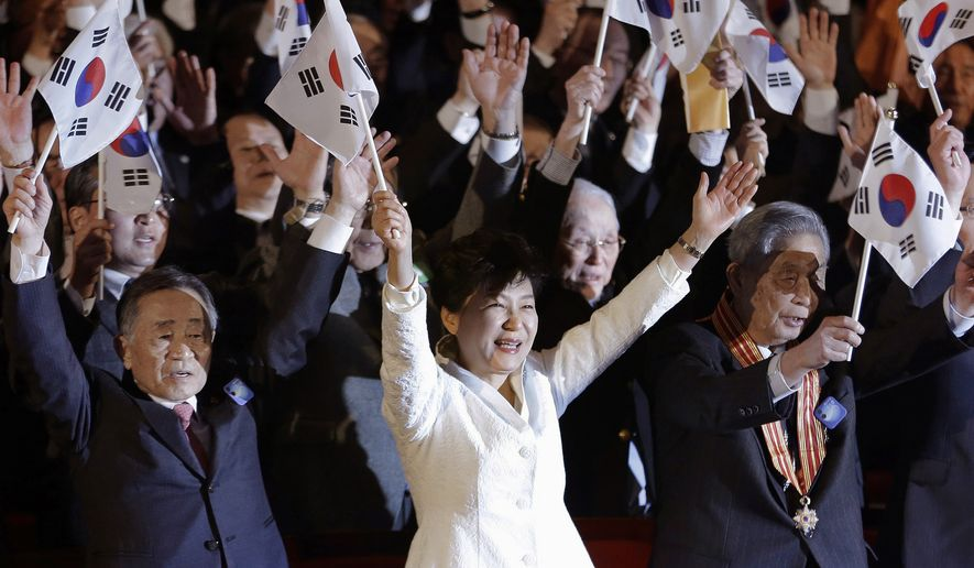 South Korean President Park Geun-hye, bottom center, gives three cheers with a national flag during a ceremony to celebrate the March First Independence Movement Day, the anniversary of the 1919 uprising against Japanese colonial rule, in Seoul, South Korea, Sunday, March 1, 2015. (AP Photo/Ahn Young-joon, Pool)