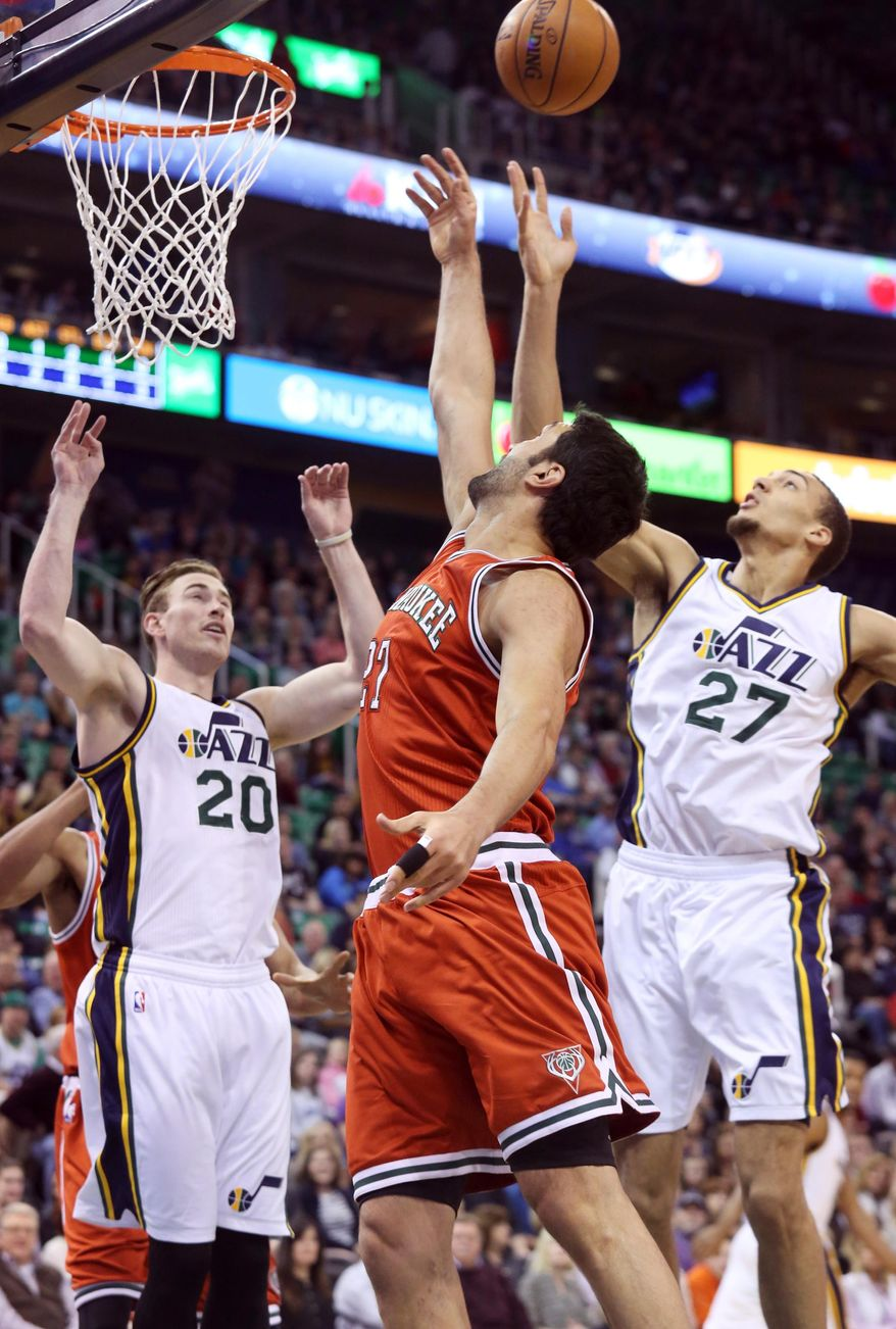 Utah Jazz's Gordon Hayward (20) and Rudy Gobert (27) compete with Milwaukee Bucks' Zaza Pachulia, center, for a rebound in the first half of an NBA basketball game on Saturday, Feb. 28, 2015, in Salt Lake City. (AP Photo/Kim Raff)