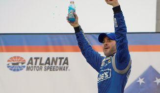 Jimmie Johnson celebrates after winning the NASCAR Sprint Cup race at Atlanta Motor Speedway on Sunday. (Associated Press)