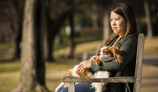 In this Feb. 25, 2015, photo, Ebola survivor Nina Pham sits in a park with her dog Bentley in Dallas. (AP Photo/The Dallas Morning News, Smiley N. Pool)