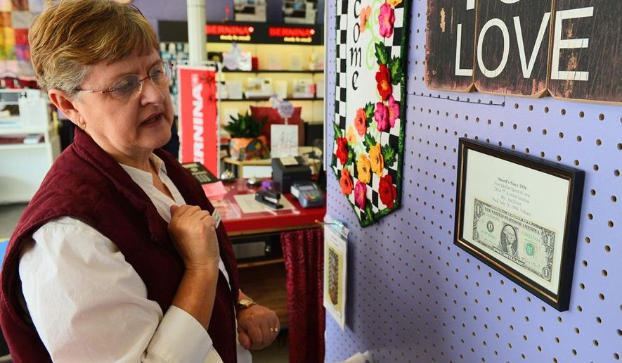 ADVANCE FOR SUNDAY MARCH 1 AND THEREAFTER - In a Feb. 22, 2015 photo, ReginiaSneed poses for a photo at Sneed's Vacuum & Sewing Center Inc. in Charleston, W.V.  Sneed's Vacuum & Sewing Center Inc. has remained in business for more than half a century by offering the personal touch. (AP Photo/The Daily Mail,  Tom Hindman)