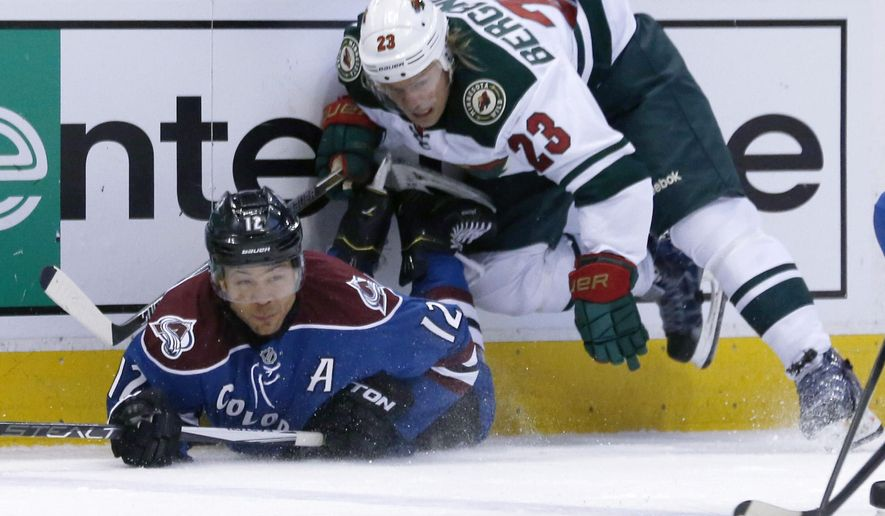 Colorado Avalanche right wing Jarome Iginla, left, falls on the ice after being checked off the puck by Minnesota Wild left wing Sean Bergenheim, of Finland, in the first period of an NHL hockey game Saturday, Feb. 28, 2015, in Denver. (AP Photo/David Zalubowski)