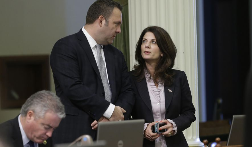 In this photo taken Friday, Feb. 13, 2015, Assemblyman Adam Gray, D-Merced talks with Assemblywoman Melissa Melendez, R-Lake Elsinore, at the Capitol in Sacramento, Calif.  Four months after California voters approved Proposition 47, which reduced penalties for certain crimes, state lawmakers and law enforcement officials are lining up to repeal portions they say went too far.  Gray and Melendez have introduced legislation that would restore the felony charge for stealing guns, if the measure is approved by the Legislature and by voters next year.(AP Photo/Rich Pedroncelli)