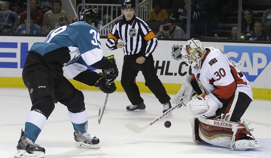 Ottawa Senators goalie Andrew Hammond, right, blocks a shot from San Jose Sharks' Logan Couture during the first period of an NHL hockey game Saturday, Feb. 28, 2015, in San Jose, Calif. (AP Photo/Ben Margot)