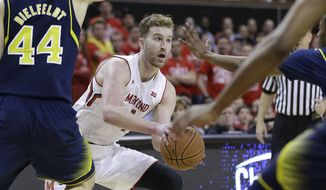 Maryland forward Evan Smotrycz looks for a teammate as he is pressured by Michigan players in the second half of an NCAA college basketball game, Saturday, Feb. 28, 2015, in College Park, Md. (AP Photo/Patrick Semansky)