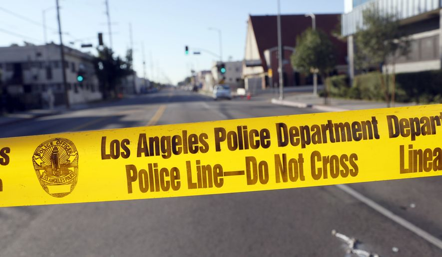 Police crime scene tape is stretched across a street in South Central Los Angeles. (Associated Press) **FILE**