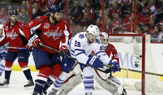Toronto Maple Leafs left wing Zach Sill (22) reaches for the puck with Washington Capitals defenseman Tim Gleason (6) and goalie Braden Holtby (70) behind, in the second period of an NHL hockey game Sunday, March 1, 2015, in Washington. (AP Photo/Alex Brandon)