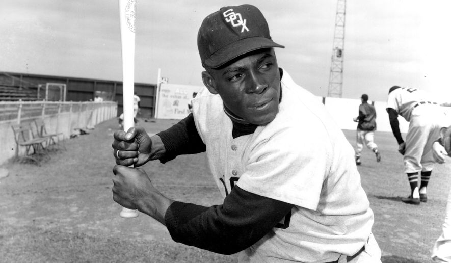 """In a March 9, 1957 file photo, Chicago White Sox outfielder Orestes """"Minnie"""" Minoso, major league baseball's first black player in Chicago, poses in batting position at Al Lopez Field in Tampa, Fla. (AP Photo, File)"""