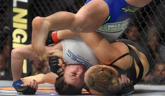 Ronda Rousey, right, grapples with Cat Zingano during a UFC 184 mixed martial arts bantamweight title bout, Saturday, Feb. 28, 2015, in Los Angeles. Rousey won after Zingano tapped out 14 seconds into the first round. (AP Photo/Mark J. Terrill)