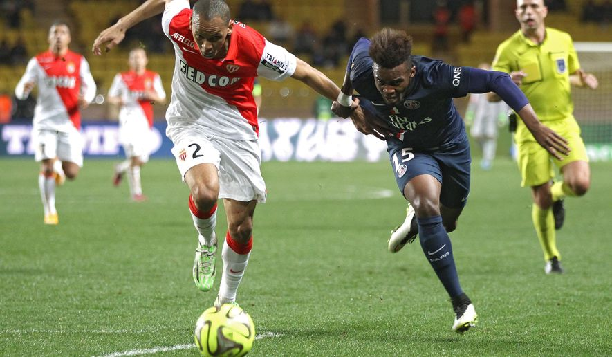 Monaco's Fabinho, left, challenges for the ball with PSG's Jean-Christophe Bahebeck, during the French League One soccer match between Monaco and Paris Saint Germain, in Monaco stadium, Sunday, March 1, 2015. (AP Photo/Lionel Cironneau)
