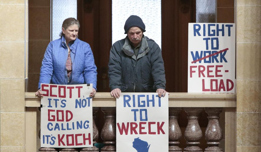 Opponents of Right to Work legislation hold signs in an upper level of the State Capitol in Madison, Wis., Monday, March 2, 2015. (AP Photo/Wisconsin State Journal, M.P. King)