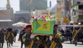 Iraqi Hezbollah fighters carry the coffin of their comrade, Ali Mansour, who his family says was killed in Tikrit fighting Islamic militants, during his funeral procession, in the Shiite holy city of Najaf, 100 miles (160 kilometers) south of Baghdad, Iraq, Monday, March 2, 2015. (AP Photo/Jaber al-Helo)