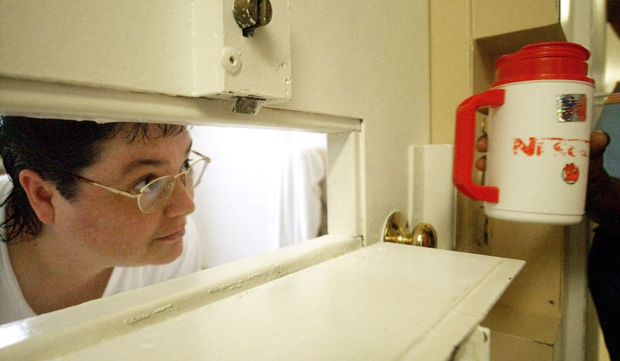 In this Tuesday, July 6, 2004, file photo, Kelly Gissendaner, the only woman on Georgia's death row, peers through the slot in her cell door as a guard brings her a cup of ice at Metro State Prison in Atlanta. Gissendaner's lawyers, on Monday, March 2, 2015, asked the Georgia State Board of Pardons and Paroles to reconsider her request to have her sentence changed to life in prison. Gissendaner, 46, is set for execution at 7 p.m. (0200 GMT) at the state prison. Gissendaner was convicted of murder in the February 1997 stabbing death of her husband. (AP Photo/Atlanta Journal-Constitution, Bita Honarvar, File)