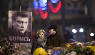 A couple comes to pay respects at the place where Boris Nemtsov, a charismatic Russian opposition leader and sharp critic of President Vladimir Putin, was gunned down on Friday, Feb. 27, 2015 near the Kremlin, in Moscow, Russia, Monday, March 2, 2015.  The investigation into the killing of Boris Nemtsov, a fierce critic of Russian President Vladimir Putin who was gunned down not far from the Kremlin, faced conflicting reports Monday about possible surveillance footage of his slaying. Words on a portrait of Boris Nemtsov reading 'Fight!' (AP Photo/Alexander Zemlianichenko)