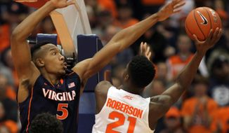 Virginia's Darion Atkins (5) puts pressure on Syracuse's Tyler Roberson, right, in the first half of an NCAA college basketball game in Syracuse, N.Y., Monday, March 2, 2015. (AP Photo/Nick Lisi)