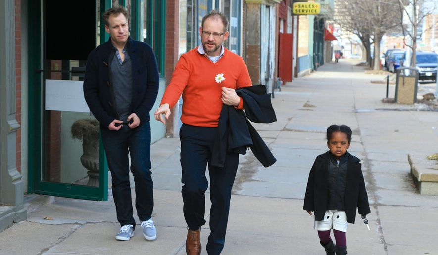 Nick Kramer, left, Jason Cadek and their 3-year-old daughter Alice leave a news conference in Omaha, Neb., Monday, March 2, 2015, convened after a federal judge blocked Nebraska's man-woman marriage law from being enforced. The men are one of seven same-sex couples who filed a lawsuit in 2014 challenging the state's voter-backed law, which doesn't recognize same-sex unions. Mr. Kramer, said he wants the ban to be overturned to give Mr. Cadek automatic custody rights for his adopted daughter. The men married in Iowa in 2013.  The Nebraska attorney general's office said it will appeal any decision blocking or overturning the marriage law. (AP Photo/Nati Harnik/File)