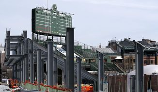 Construction of the left field bleachers and new video board continues while the Chicago Cubs' press forward on renovations to Wrigley Field as opening day approaches Monday, March 2, 2015, in Chicago. Chicago Cubs officials plan to ask the city for permission to work around the clock to speed up Wrigley Field renovations. (AP Photo/Charles Rex Arbogast)