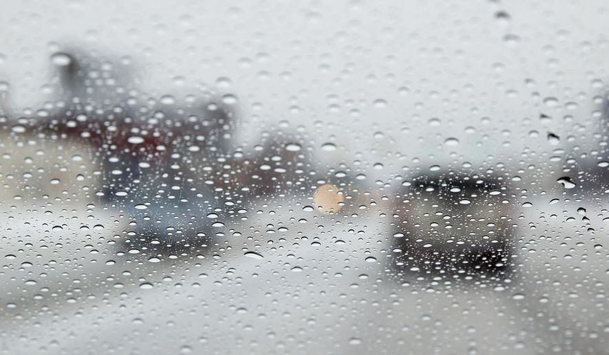 Precipitation is shown on a windshield in Detroit Tuesday, March 3, 2015. Driving conditions are slippery in Michigan amid a wintry weather mix. A combination of snow, sleet and freezing rain is expected throughout the day. (AP Photo/Paul Sancya)