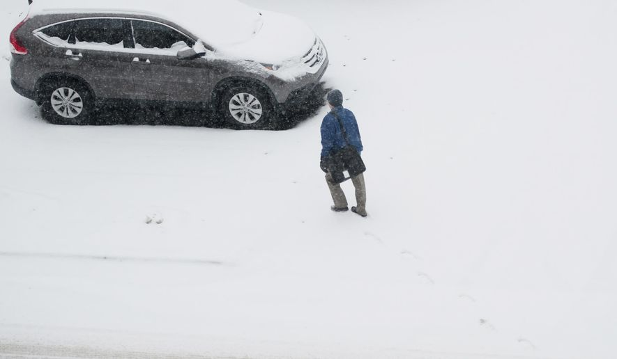 A man walks to his car in downtown Jackson, Mich., during a snowstorm on Tuesday morning, March 3, 2015. (AP Photo/The Jackson Citizen Patriot-MLive Media, J. Scott Park) ALL LOCAL TELEVISION OUT; LOCAL TELEVISION INTERNET OUT