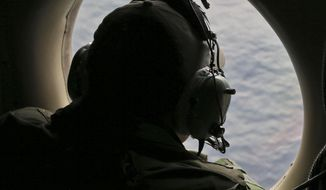 In this Saturday, March 22, 2014, file photo, flight officer Rayan Gharazeddine on board a Royal Australian Air Force AP-3C Orion, scans for the missing Malaysia Airlines Flight MH370 in southern Indian Ocean, Australia. (AP Photo/Rob Griffith, Pool)