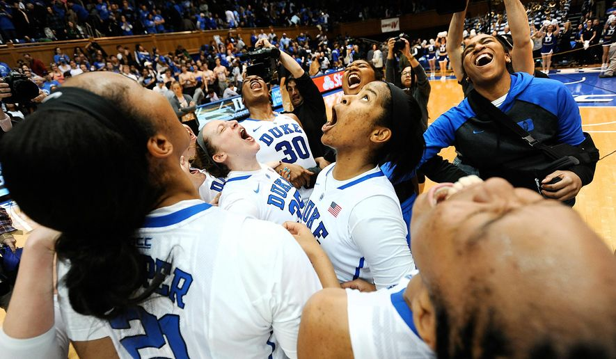 Duke women's basketball players, including Amber Henson (30), Jenna Frush (35),  Ka'lia Johnson (14), react after defeating North Carolina 81-80 on Sunday, March 1, 2015 at Cameron Indoor Stadium in Durham, N.C.   (AP Photo/The Herald-Sun, Christine T. Nguyen)